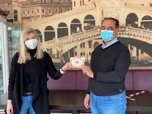 Vivian Jessen nimmt stellvertretend für den Gewinner den Gutschein von Restaurantleiter Afzaal Ahmed entgegen(c) Stadtmarketing Uelzen
